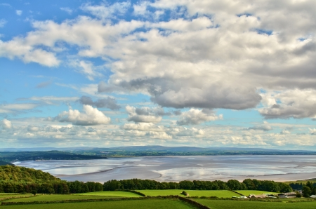 View over lush green farmland towards the Morecambe Bay estuary in England on a sunny day with cumulus clouds Stock Photo - 15938217