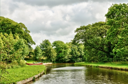 Tranquil view of the Lancaster Canal, England near Borwick with a canoe or kayak pulled up on the lush green bank Stock Photo - 16004537
