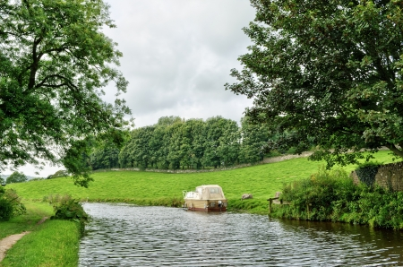 Boat moored on the Lancaster Canal, England, near Borwick as it meanders through lush green countryside Stock Photo - 16004522
