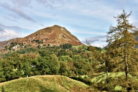 deciduous woodland: Helm Crag in the English Lake District, set against a blue sky with wispy clouds, viewed from a grassy knoll, within a landscape of mixed deciduous woodland and larch trees