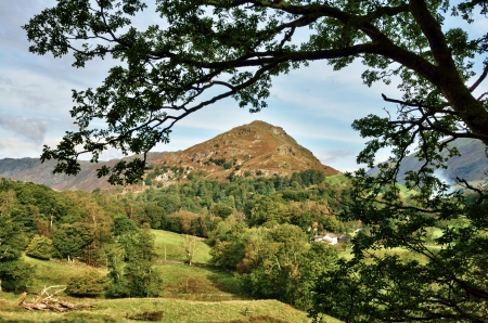 A view of Helm Crag in the English Lake District, across a wooded landscape, set against a blue sky with an arching frame of leafy branches  Stock Photo - 16218343