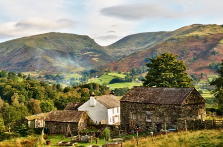 A traditional whitewashed Farmhouse with associated stone built barns, set in a wooded landscape against a picturesque backdrop of Red Screes and Fairfield, in the English Lake District  Stock Photo - 16206306