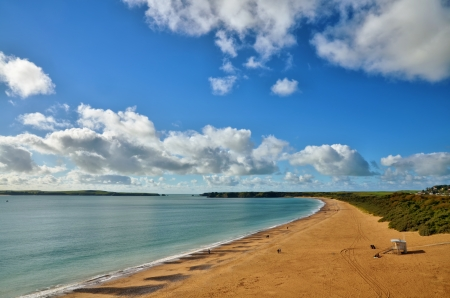 tenby wales: Panoramic view of South Beach, Tenby, curving towards Giltar Point and Caldey Island, with a blue sky and cumulus clouds