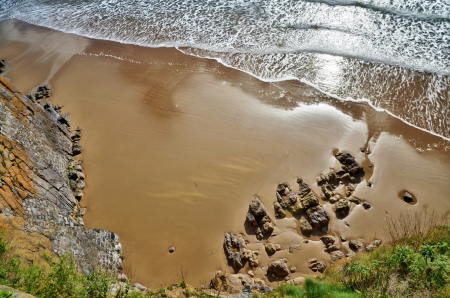 An aerial view of a sandy cove on South Beach at Tenby, looking down onto rocks, with coastal vegetation and foaming waves cascading across the wet rippled sand  Stock Photo - 16409172