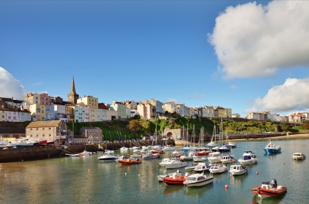 View of the picturesque curve of Tenby harbour and town, with boats peacefully moored, on a lovely summers day