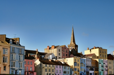 Longitudinal view of picturesque houses in Tenby, with pastel painted facades, and St Marys Church Stock Photo