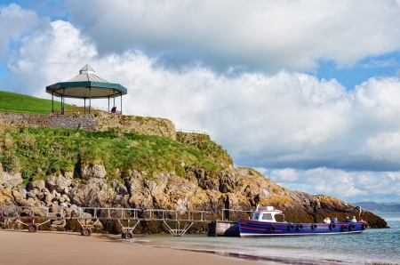 tenby wales: Picturesque view of a bandstand, perched on a rocky promontory jutting into the sea at Tenby, Wales, with a boat moored below on Castle Beach  Stock Photo