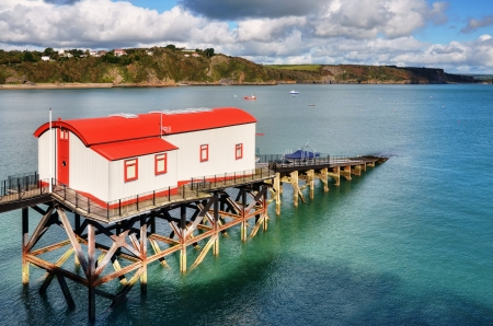 slipway: Beautiful view of a brightly painted,converted Lifeboat Station, with slipway stretching away into an undulant sea,at Tenby, Wales  Stock Photo