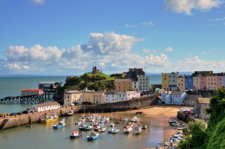 slipway: Picturesque view of boats in Tenby Harbour, with its clusters of colourful painted houses, and Castle Hill