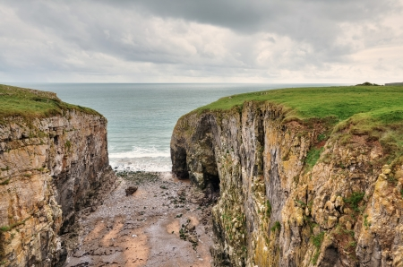 carboniferous: A view of Raming Hole, a coastal cleft formed from a weakness in the carboniferous limestone cliffs, at Stackpole, Pembrokeshire
