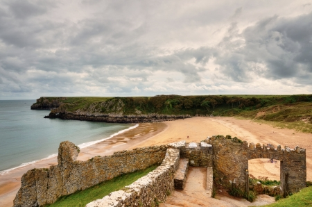 The curve of Barafundle Bay on the Stackpole Estate, Pembrokeshire, with a ruined structure in the foreground and gentle waves rolling onto the sandy beach Stock Photo - 16720545