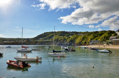 Boats on a rippled sea, in the tranquil haven of New Quay harbour, Ceredigion, Wales, with a cloud strewn sky reflecting in the water  Stock Photo - 16850739