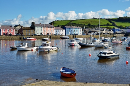slipway: Boats in Aberaeron Harbour, Wales, with colourful regency style houses lining the quayside, against a backdrop of a grassy hillside