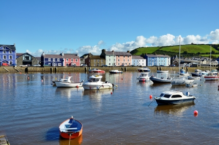 colourfully: View of picturesque colourfully painted houses lining the quayside at Aberaeron Harbour, Ceredigion, Wales, with boats moored on the tranquil water, on a beautiful summers day  Stock Photo