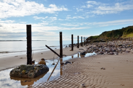 A line of posts running along a beach with pebbles, and rippled sand, set again a blue sky with clouds Stock Photo - 17007262