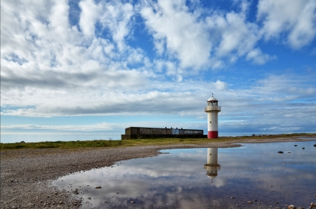 View of a lighthouse on the curving coastline near Millom, Cumbria, reflected in a tranquil sea, set against a blue sky with cumulus clouds Stock Photo - 17007261