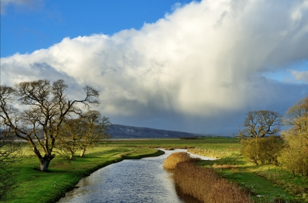 The River Bela at Milnthorpe, winding towards Morecambe Bay on a winters day, with a shaft of sunlight on the banks, and Cumulonimbus clouds Stock Photo - 17007264