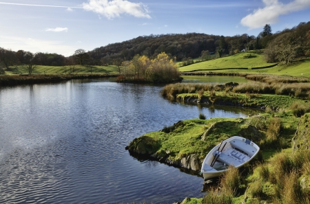 A small boat moored on the shores of a tranquil lake in the Winster Valley, situated in the English Lake District, on a peaceful sunny day Stock Photo - 17071361