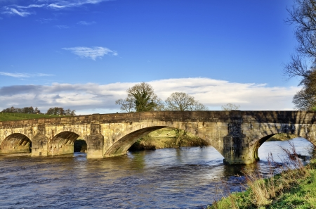 A view of Eadsford Bridge in Clitheroe, Lancashire; a nine span medieval bridge dating from c1339, crossing the River Ribble, set against a blue sky Stock Photo - 17380408