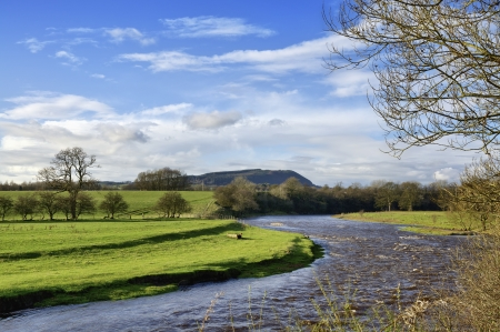 A view of the curving River Ribble wending its path through fields near Clitheroe, Lancashire, with Longridge Fell in the distance, on a sunny autumn day