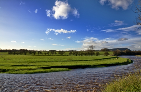 A peaceful view of the River Ribble, near Clitheroe, Lancashire, running through verdant green meadows, and set again a blue sky with clouds, on a sunny autumn day Stock Photo - 17462072
