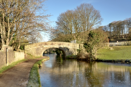 Picturesque view of the Lancaster Canal and towpath, looking towards bridge number 124 on a sunny winters day, with trees reflected in the water Stock Photo - 17990968