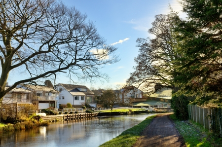 Picturesque view of the Lancaster Canal and tree lined towpath, wending its way past waterside houses at Bolton-Le-Sands on a beautiful sunny winters day Stock Photo - 17990975