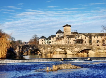 cumbria: View of the River Kent flowing under Stramongate Bridge, Kendal, with tree lined bank, weir and a backdrop of riverside buildings on a sunny winter morning  Stock Photo