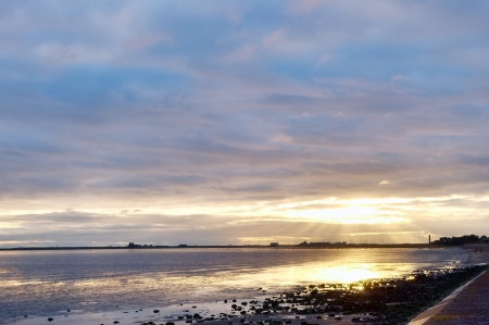 Sunset over Morecambe Bay at Roosebeck, Cumbria, looking towards Roa Island and silhouetting The Needle, with the last rays of sunlight breaking through the evening clouds   Stock Photo - 18232767