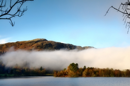 Tranquil view of an island on Grasmere, with Silver Howe behind, on a misty winter morning in the English Lake District Stock Photo - 18234284