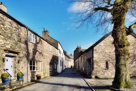 View of a picturesque street with cottages, and a tree set against a blue sky, in the village of Cartmel, Cumbria, England, on a sunny winter afternoon  Stock Photo - 18367135