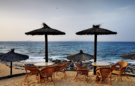Restaurant chairs and tables standing on a sandy beach alongside the ocean on a sunny day on Lanzarote in the Canary Islands Stock Photo - 18447026