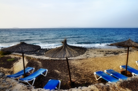 Beach on the Canary Islands with comfortable recliner chairs under thatched umbrellas overlooking a tropical ocean for a peaceful summer holiday Stock Photo - 18517397