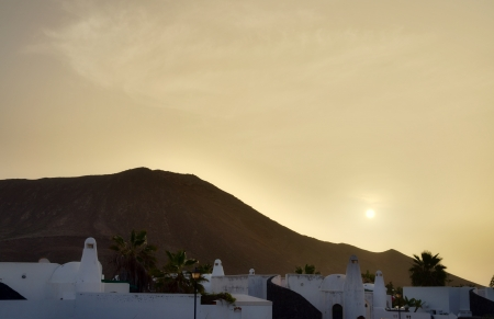 Whitewashed buildings in Lanzarote on the Canary Islands at dusk or dawn with the sun peeping through a hazy sky casting a golden light Stock Photo - 18517396