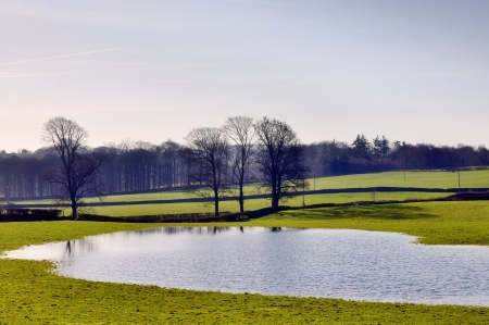 View of a flooded field on farmland with woodland and trees on a sunny winter morning in the English countryside  Stock Photo - 18517399
