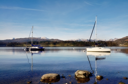 Peaceful view of two boats moored on Lake Windermere, on a sunny winters morning in the English Lake District, with rocks prView of Lake Windermere with two boatsotruding from the shallow waters edge   Stock Photo - 18563891