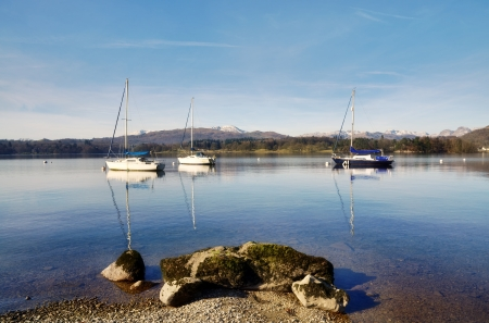 Three boats moored on Lake Windermere, with rocks on the foreshore, on a sunny winter day in the English Lake District Stock Photo - 18597159