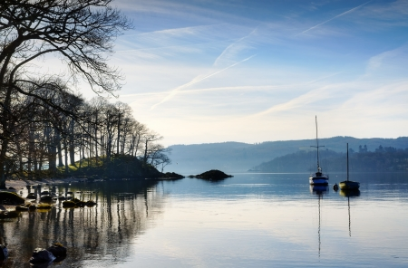 Beautiful view of a winter morning on Windermere in the English Lake District, with sunlight filtering through filigree branches and two boats calmly reflected in the water, set against a blue sky     Stock Photo - 18674941