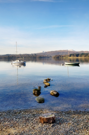 Peaceful view of two boats moored on Lake Windermere, on a sunny winters morning in the English Lake District, with rocks and a tree stump in the foreground Stock Photo - 18785297