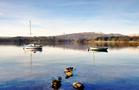 Tranquil view of two boats moored on Lake Windermere, against a backdrop of Coniston Old Man and Wetherlam, on a sunny winters morning in the English Lake District, with rocks in the shallow water  Stock Photo - 18785280