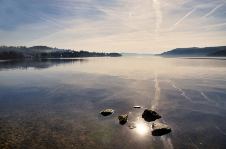 lake district: Beautiful reflections of sky and clouds in Windermere,situated in the English Lake District on a tranquil winter morning,  with sunlight glancing off the water Stock Photo