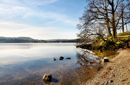 Tranquil view of trees and pebble strewn shore of Windermere, with calm reflections in the clear waters, on a sunny winter morning in the English Lake District Stock Photo - 18785313