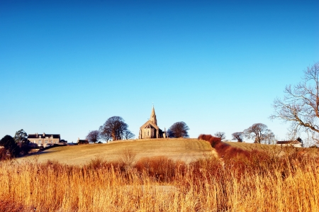 View of Holy Trinity Church, Bardsea, Cumbria on a winter morning, set against a clear blue sky with long grasses in the foreground Stock Photo - 18925070