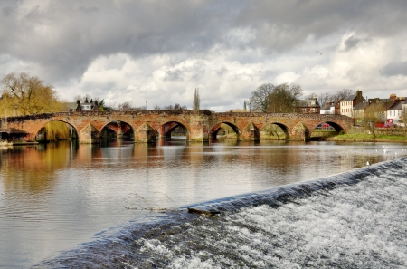 View of the historic 15th Century Devorgilla Bridge spanning the River Nith, with water cascading over the weir, on a winters day in Dumfries, Scotland Stock Photo - 18925073