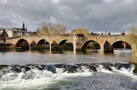 span: Devorgilla Bridge, a 15th century crossing on the River Nith, with water flowing over the weir, on a winters day in Dumfries, Scotland