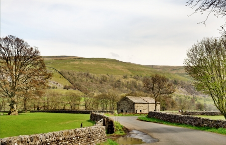 A country lane and stone built barn in the Yorkshire Dales, England, bordered by fields and set again a backdrop of fells Stock Photo - 19972239