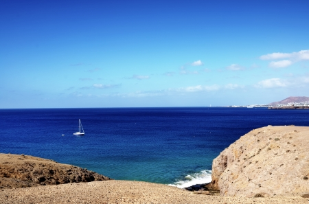 Boat sailing in sea off volcanic landscape of Lanzarote, Canary Islands, Spain Stock Photo - 19972243