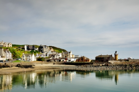 View of houses lining Portpatrick harbour in southwest Scotland,with reflections in the water on a calm summers day Stock Photo - 20502886