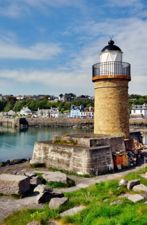View of the lighthouse and harbour at Portpatrick in southwest Scotland, set against a blue sky with clouds on a summers day Stock Photo - 20502889