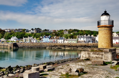 View of the lighthouse and harbour lined with colourful houses at Portpatrick in southwest Scotland on a summers day